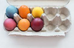 Easter vibes. Top view of colored Ester eggs in paper container. royalty free stock photography