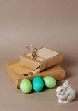 Easter vintage still life. Vintage still life with easter eggs, white bunny and gift boxes in craft paper Royalty Free Stock Photo