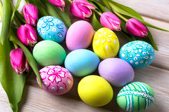 Easter vivid colors hand painted eggs. Easter vivid colors purple, blue, pink, green, yellow hand painted eggs and tulips. Happy Easter greeting card or stock image