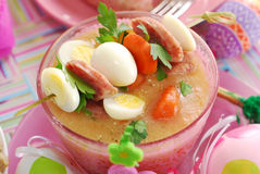 Easter white borscht with quail eggs and sausage in pink glass Royalty Free Stock Photos