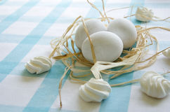 Easter white eggs and meringue on a  blue tablecloth Royalty Free Stock Photos
