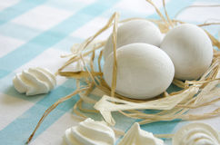 Easter white eggs and meringue on a  blue tablecloth Stock Photos