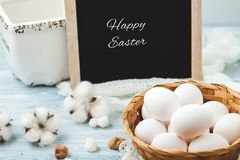 Easter white eggs in a wicker basket on a light background Background for a postcard. Easter white eggs in a wicker basket on a light background Background for Royalty Free Stock Images