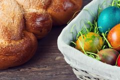 Easter wicker basket with colored eggs and Easter bread on grey wooden board. Stock Photos