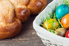Easter wicker basket with colored eggs and Easter bread on grey wooden board. Stock Photography