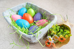 Easter wicker basket with colored eggs and a bunch of spring flowers on white board. Stock Photos