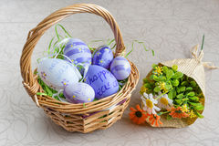 Easter wicker basket with colored eggs and a bunch of spring flowers on white board. Royalty Free Stock Images
