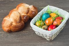 Easter wicker basket with colored eggs and Easter bread on grey wooden board. Royalty Free Stock Photos