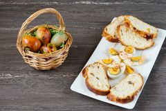 Easter wicker basket with colored eggs and sliced Easter bread in white plate on grey wooden board. Stock Photography