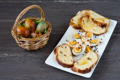 Easter wicker basket with colored eggs and sliced Easter bread in white plate on grey wooden board. Stock Image