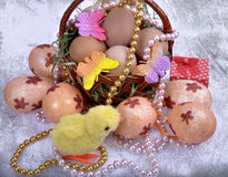 Easter wicker basket with colored eggs and a small chicken Stock Photos