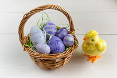 Easter wicker basket with colored eggs and a small chicken on wooden board. Royalty Free Stock Images