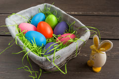 Easter wicker basket with colored eggs and a small egg rabbit on grey wooden board. Stock Photography