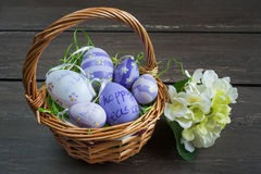 Easter wicker basket with colored eggs and a small white flower on grey wooden board. Royalty Free Stock Image