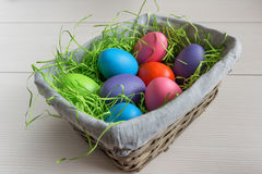Easter wicker basket with colored eggs on wooden board. Stock Photography