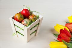 Easter wicker basket with colored eggs and yellow and red tulips on white wooden board. Royalty Free Stock Photo