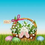 Easter wicker basket with rabbit and flowers Stock Images