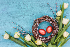 Easter willow wreath, Easter eggs and white tulips on blue background. Top view Stock Images