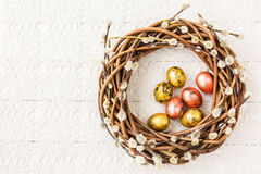 Easter willow wreath and quail  Easter eggs on white tablecloth. Top view Stock Photography