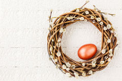 Easter willow wreath with red Easter egg on white tablecloth. Top view. Copy space royalty free stock photos