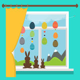 Easter window with garlands of colored Easter eggs. Set of chocolate rabbits on the windowsill Royalty Free Stock Image