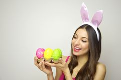 Easter woman concept. Cute girl with bunny ears looking to her egg carton of colorful Easter eggs on white background. Copy space Stock Photo