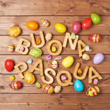 Easter wooden letter composition. Words Buona Pasqua as Happy Easter in italian language made of wooden letters and surrounded with multiple egg decorations as a royalty free stock photos