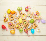 Easter wooden letter composition. Words Buona Pasqua as Happy Easter in italian language made of wooden letters and surrounded with multiple egg decorations as a stock image
