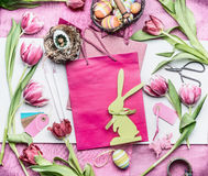 Easter workspace in pink color:  tulips flowers and accessories for easter decorations making with eggs, paper bags and basket, to Royalty Free Stock Photo