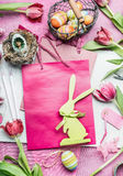 Easter workspace with rabbit and tulips in pink color. Flowers and accessories for easter decorations making with eggs Royalty Free Stock Images