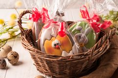 Easter wrapped cookies in a brown wicker basket near quail eggs and blossoming branch stock images