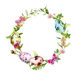 Easter wreath with colored eggs in grass, flowers. Round frame. Watercolor Royalty Free Stock Photos