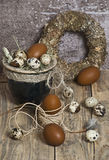 Easter wreath, eggs in a clay pot, brown eggs, quail eggs, chicken feathers, stock photo