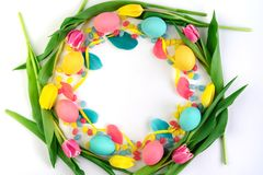 Easter wreath made of yellow tulips, colorful eggs and candies on white background. Flat lay. stock photo