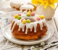 Easter yeast cake Babka covered with icing and decorated with marzipan eggs on a white plate on a wooden table. stock photography