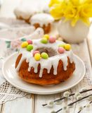 Easter yeast cake Babka covered with icing and decorated with marzipan eggs on a white plate on a wooden table. royalty free stock photo