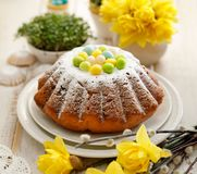 Easter yeast cake sprinkled with powdered sugar, decorated with marzipan eggs. royalty free stock images