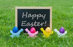 Greeting card for a Happy Easter. Eastercard with chalkboard and colorful Easter eggs in egg cups  on a meadow Royalty Free Stock Image