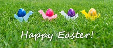 Colorful Easter eggs and text: happy easter. Eastercard with colorful Easter eggs in egg cups Royalty Free Stock Photos