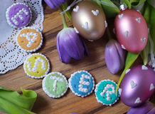 Easteregg  cookies words alphabet wood background message tulips flowers Royalty Free Stock Images