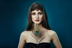 Eastern Arab woman with a peacock feather in her hands near her face. Beauty fashion makeup Arab women, big beautiful eyes. royalty free stock photos