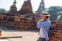 Eastern Asia summer holidays. Caucasian man tourist from back looking at Wat Chaiwatthanaram temple. Travelers take pictures with. DSLR cameras. Travel in old stock images