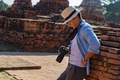 Eastern Asia summer holidays. Caucasian man tourist from back looking at Wat Chaiwatthanaram temple. Travelers take pictures with. DSLR cameras. Travel in old stock image