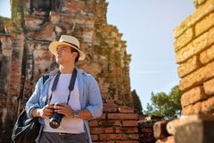 Eastern Asia summer holidays. Caucasian man tourist from back looking at Wat Chaiwatthanaram temple. Travelers take pictures with. DSLR cameras. Travel in old stock photography