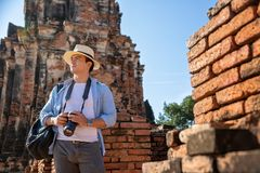 Eastern Asia summer holidays. Caucasian man tourist from back looking at Wat Chaiwatthanaram temple. Travelers take pictures with. DSLR cameras. Travel in old royalty free stock images