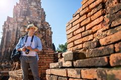 Eastern Asia summer holidays. Caucasian man tourist from back looking at Wat Chaiwatthanaram temple. Travelers take pictures with. DSLR cameras. Travel in old stock photo