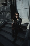 Eastern beautiful woman wearing biker jacket poses in backyard of vintage apartment house Royalty Free Stock Photos
