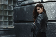 Eastern beautiful woman wearing biker jacket poses in backyard of vintage apartment house royalty free stock photography