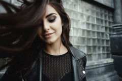 Eastern beautiful woman wearing biker jacket poses in backyard of vintage apartment house Royalty Free Stock Images
