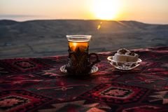 Eastern black tea in glass on a eastern carpet. Eastern tea concept. Armudu traditional cup. Sunset background. Royalty Free Stock Photos